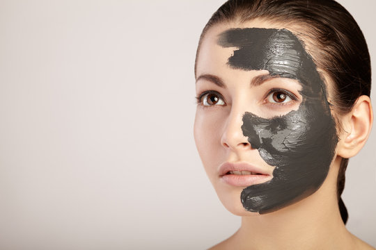 Beautiful girl with clay mask on her face