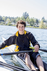 Mixed race teenage boy rowing scull on lake