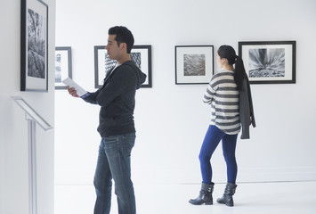 People admiring photograph art in gallery