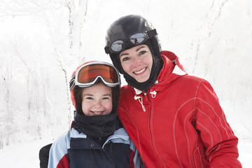 Caucasian mother and daughter smiling in snow