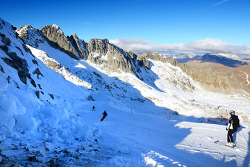 The ski slope and skiers at Presena glacier ski area, Italy.
