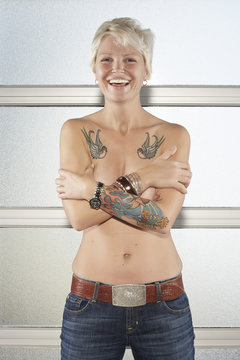 Caucasian woman with bare chest showing off tattoos