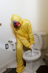 Woman dressed in Haz Mat to clean toilet