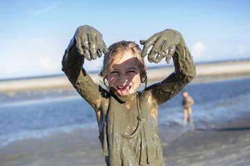 Caucasian girl playing in mud on beach