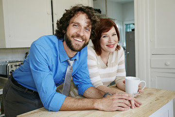 Pregnant Caucasian couple smiling in kitchen