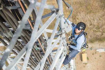 Hispanic electrician climbing on cell tower