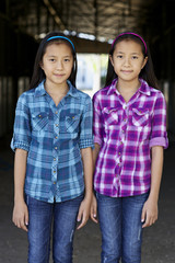 Asian twin girls smiling in barn