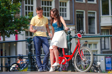 Happy family vacation on bikes in old streets in Amsterdam