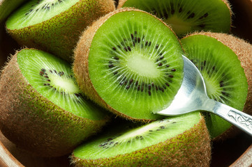 Juicy ripe kiwi fruit in wooden bowl with spoon