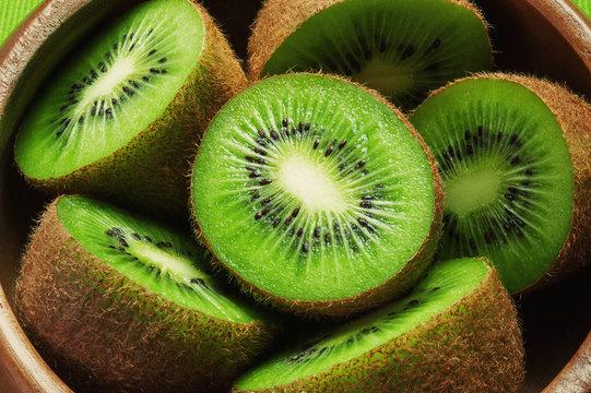 Juicy ripe kiwi fruit in wooden bowl