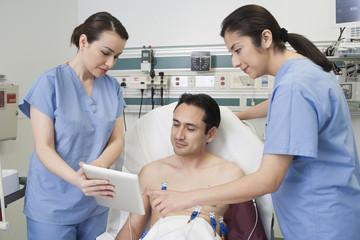 Nurses and patient using digital tablet in hospital