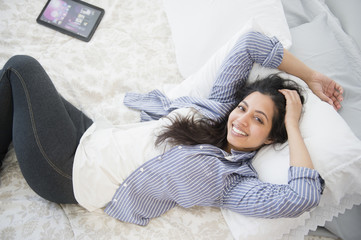 Portrait of smiling Asian woman laying on bed