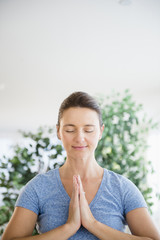 Serene Caucasian woman with hands in prayer position