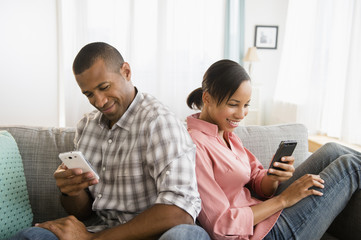 Couple using cell phones back to back on sofa
