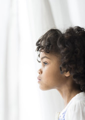 Close up of pensive African American girl looking out window