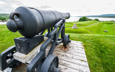 Old guns of yester year, a cannon overlooking lands they once defended, from the 18th century, sits on its display platform, never to fire again.  Spring day in Nova Scotia.