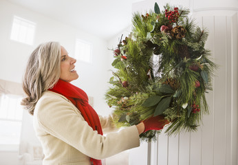 Caucasian woman hanging Christmas wreath on door