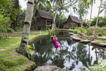 Caucasian girl swinging on rope in garden, Ubud, Bali, Indonesia