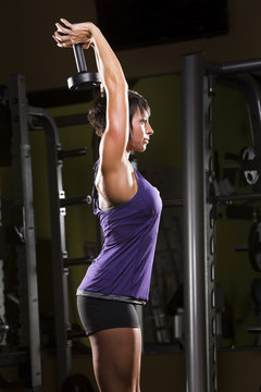 Caucasian woman doing triceps extensions with dumbbell in gym
