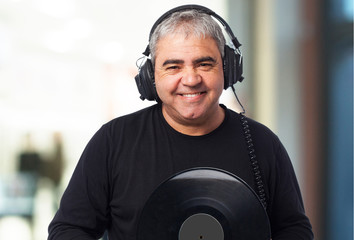 portrait of a mature man listening to music and holding a vinyl