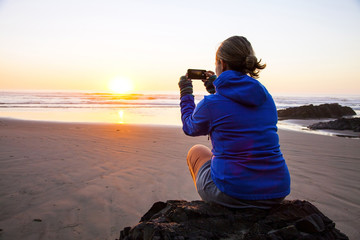 Caucasian woman taking picture of sunrise on beach