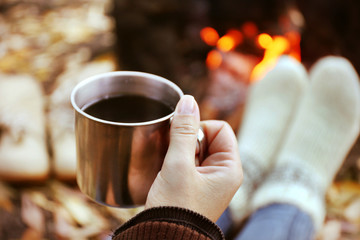 Woman sitting beside the fire with a cup of coffee, closeup