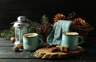 Two mugs of hot cacao with marshmallow and gloves on black table