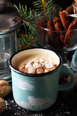 Mug of hot cacao with marshmallow, cookies and lantern on black table