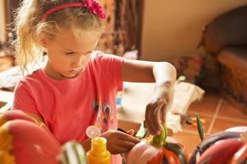 Caucasian girl decorating jack o'lantern