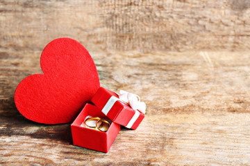 Red heart and wedding rings in a box on wooden background closeup