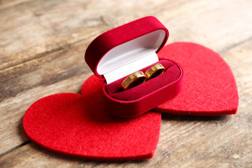 Two red hearts and wedding rings in velvet silk box on wooden background closeup