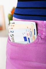 Euro money in pocket violet pants on unfocused background closeup