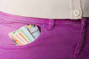Folded euro money in pocket violet pants closeup