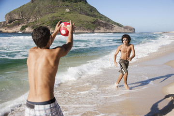Men playing with soccer ball in surf on beach
