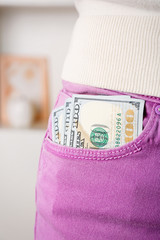 Dollars in the pocket of violet pants on unfocused background, closeup