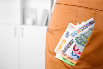Euro money in pocket of brown pants on unfocused background closeup