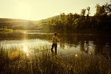 Caucasian man fishing in still lake