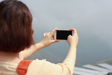 Back view of woman taking photograph with smart phone camera