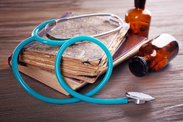 Books, pills and stethoscope on wooden table closeup