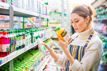 Concentrated woman choosing agricultural chemicals for flowers and plants