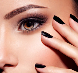 Woman's eye with pink eye makeup and nails