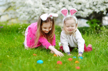 Two little sisters hunting for easter egg on Easter day
