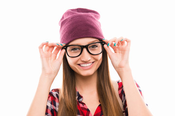 Close up portrait of girl in cap touching her glasses