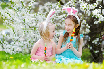 Two adorable little sisters eating colorful gum candies on Easter