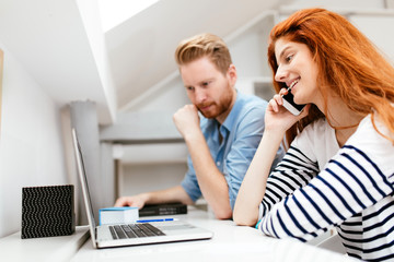 Beautiful ginger woman working in office with colleague