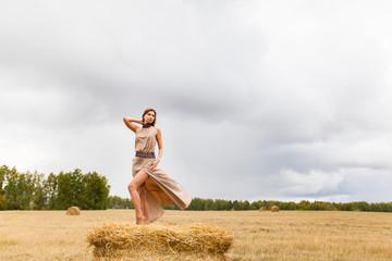 Молодая красивая девушка стоит на стоге сена