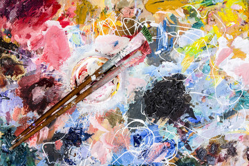 The artist palette with a Cup of mixing oil paints and two brush