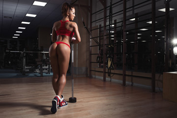 Sexy beautiful athletic woman posing after sport exercise in gym
