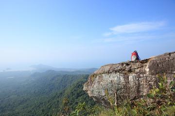 hiking backpack and sticks on mountain peak