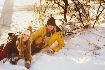 Couple play in winter with snow and sledges